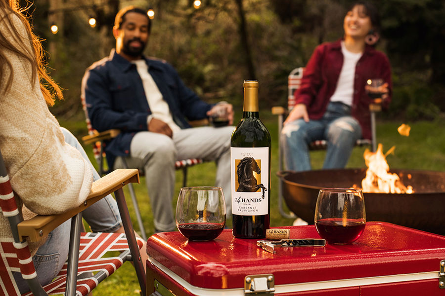 Three people around a fire holding glasses of wine