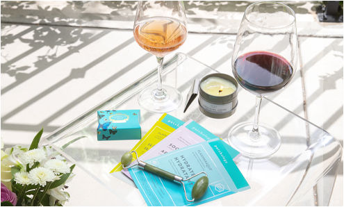 A glass of rosé and red surrounded by a lit candle, jade roller, face masks, and luxury soap